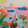 Reese George, 6, paints a mural in the hallway at Bridges Elementary School. The mural is being painted by the after school group Art Club run by art teacher Amy Muehlenhardt. Photo by Jackson Forderer
