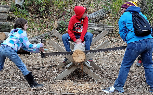 A trio of children work together to cut a chunk off of a log the old fashioned way during History Fest.