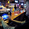 Mully's on Madison bartender Krista Johnson demonstrates how to use one of the bar's four iPad-based electronic pull tab machines Thursday. Mully's is the first Mankato bar to feature the newest style of charitable gambling.