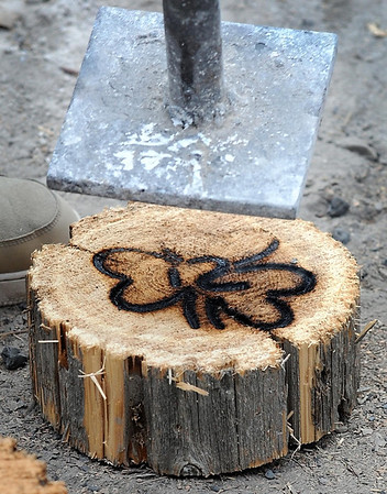 A volunteer brands a log with a hot iron.