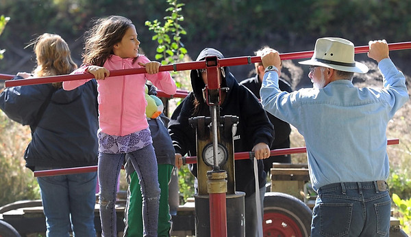 Pat Christman <br /> Clara Jane Blume, 8, left, gets some help pumping a hand pumped fire hose form Tom Allen during History Fest Saturday at the Jack McGowan farm near Mankato.