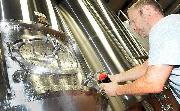 Pat Christman <br /> Manakto Brewery co owner Tim Tupy taps a sample of the brewery's mint stout beer from a tank at the brewery Friday. The brewery's holiday offering cannot be bottled until the labels are approved, which cannot be done during the federal government shutdown currently underway.