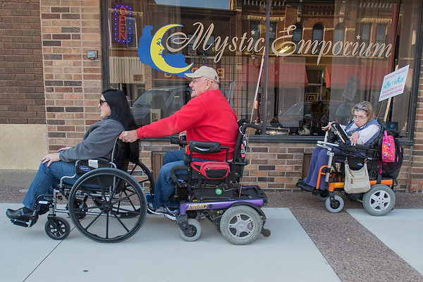 Trudy Kunkel (left), a Mankato City Council member, gets a boost from Mike Lundgren (center) followed by Juile Fales on a sidewalk in downtown Mankato during the SMILES Wheelchair awareness event. Photo by Jackson Forderer