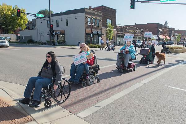 Trudy Kunkel (left), a Mankato City Council member leads a line of people in wheelchairs during a SMILES awareness event on Friday in downtown Mankato. Photo by Jackson Forderer