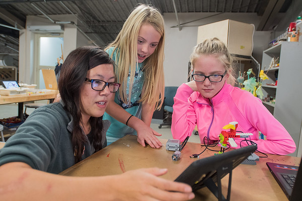 Karmy Luker (left) helps Breena Luiken (center), 8, and Hailee Guth, 11, work on a robotic Lego bird by looking at the setup on an iPad at the Children's Museum of Southern Minnesota on Wednesday. The museum hosted the International Day of the Girl, a partnership between the museum, Vex Robotics, ISD 77 and the Army, which inspired girls to become interested in STEM with eight different activities. Photo by Jackson Forderer