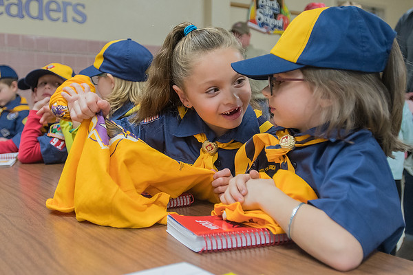 Kiera Hutchens (second from right) talks with Finnigan Wenner, 7, after they received t-shirts for being new members of the Boy Scouts, Pack 91, at Washington Elementary on Thursday. This is the first year that girls can join the Boy Scouts of America. Photo by Jackson Forderer