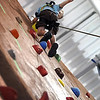 Zane Stempka, 3, waves to his parents after making it to the top of MSU's new indoor climbing wall.