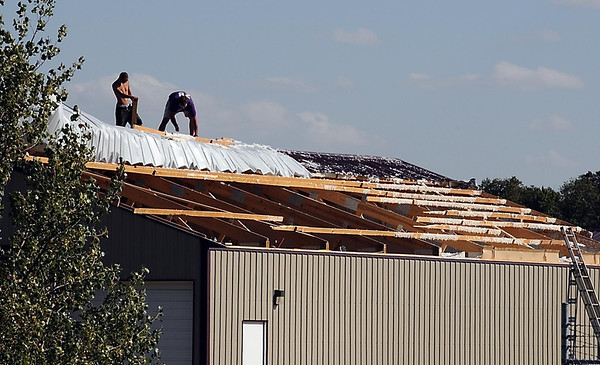 Workers remove damaged roof panels from a building owned by Reichel Insulation Wednesday afternoon south of Mankato. A late evening storm caused isolated damage throughout southern Minnesota.