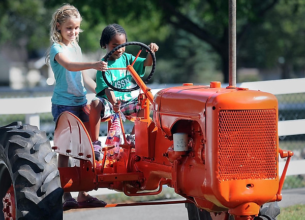 Morgan Bakke (left) and Zaccheaus Green play on a restored Allis Chalmers C model tractor in Sibley Park that was donated by the Le Sueur County Pioneer Power Assocation.