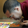 A monk carefully places sand on a mandala Wednesday.