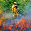 John Cross<br /> A member of a Minnesota Department of Natural Resources burn shimmers through the flames and heat of a prescribed burn of 53 acres of Minneopa State Park on Tuesday. The purpose of the burn was to spur the growth of grasses and forbs and to clean out dead materials.