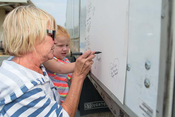 Carolyn (last name withheld) helps Isla Barrett, 3, write a message to those affected by Hurricane Harvey. Those who have donated to Fill That Truck! have started a message board that will be sent to Houston, along with a semi-trailer full of donated supplies. Photo by Jackson Forderer