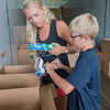 Ashley Bullerman and Landyn Bullerman, 10, unwrap a donated package of toothpaste boxes in a semi-trailer in the parking lot of New Creation Church on Friday. The donations will be delivered to those affected by Hurricane Harvey in Texas. Photo by Jackson Forderer
