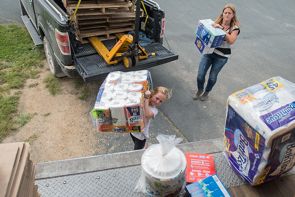 Hailey Levos (left), 8, loads a donated bundle of paper towels onto the back of a semi trailer in the parking lot of New Creation Church on Friday. Tina McClain (right) is organizing Fill That Truck! for those affected by Hurricane. McClain said individual and businesses donations are welcome for the semi trailer that will close on Thursday night. Donation times can be found on the Facebook page Fill That Truck! Photo by Jackson Forderer