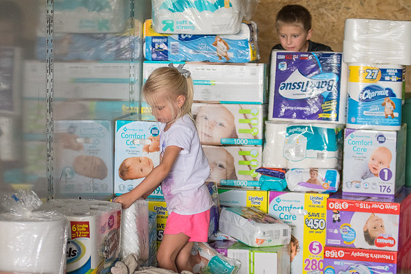 Tassyn Bullerman (left), 4, organizes the diaper section of a semi-truck being filled with donations for those affected by Hurricane Harvey as Caleb McClain, 9, looks on. Tina McClain, the organizer of Fill That Truck! said they are in need of diapers, baby wipes, cleaning supplies and feminine products. Photo by Jackson Forderer