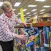 Jennifer Cassman, a library specialist at the Blue Earth County Library, puts a book back on the shelf in the children's section of the library. Photo by Jackson Forderer