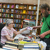 John Noel (right) mulls over what videos to purchase with input from Joellen Finch at the Pages Past bookstore located in the Blue Earth County Library. Photo by Jackson Forderer