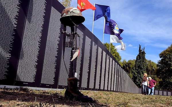 Visitors look for names on a traveling Vietnam veterans memorial wall Thursday at the Vietnam Veterans Memorial site along Stoltzman Road.