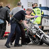 A St. Peter police officer and Minnesota State Patrol trooper turn a motorcycle upright as emergency crews tend to its rider after a crash Wednesday on Highway 22 near Kasota.