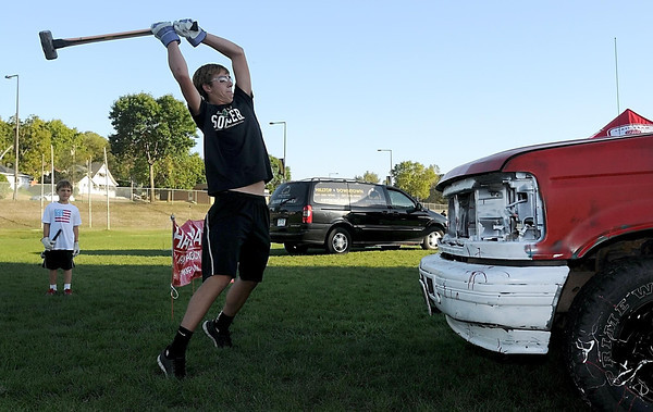 Mankato West junior Alex Denhof takes a swing at a pickup truck with a sledgehammer during a Celebrate My Drive teen driving safety event before Friday's football game at West. During the event sponsored by State Farm Insurance, students who signed a pledge not to text and drive and donated a dollar could take two swings at the truck with the hammer.