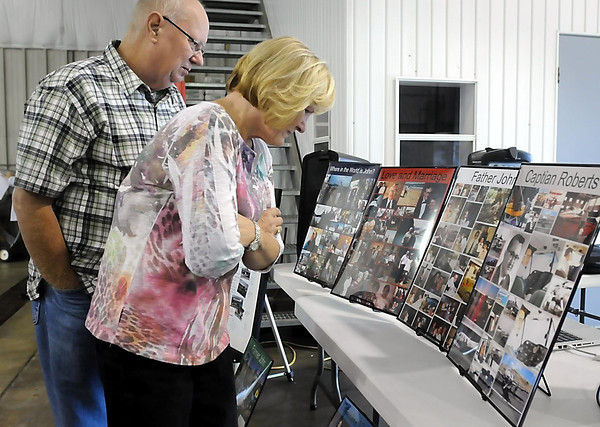 Perry and Jo Brown of Mankato view photographs of John Roberts during a fly-in/drive-in breakfast held Wednesday at the Mankato Regional Airport in honor of the Minnesota State University aviation teacher/mentor who died last week. People flew in from as far away as Texas to attend to event which preceded Roberts' funeral service.