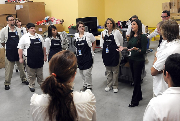 Goodwill store manager Sara Quast gives the employees a final pep talk before the store's three-hour opening Friday. The store employs 35 people in part- or full-time positions.