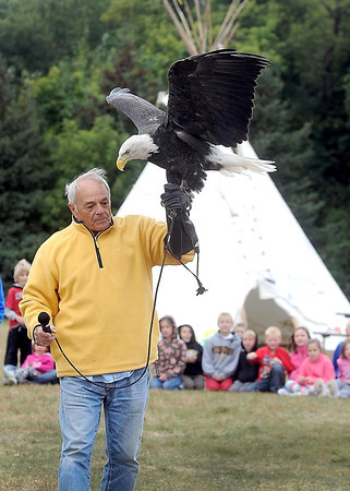 """National Eagle Center volunteer Pat Daddario holds up a female bald eagle named """"Angel"""" as he answers questions from schoolchildren during Education Day at the 39th Annual Mahkato Wacipi (Powwow) Friday at Land of Memories Park. The powwow continues through Sunday."""