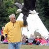 "National Eagle Center volunteer Pat Daddario holds up a female bald eagle named ""Angel"" as he answers questions from schoolchildren during Education Day at the 39th Annual Mahkato Wacipi (Powwow) Friday at Land of Memories Park. The powwow continues through Sunday."