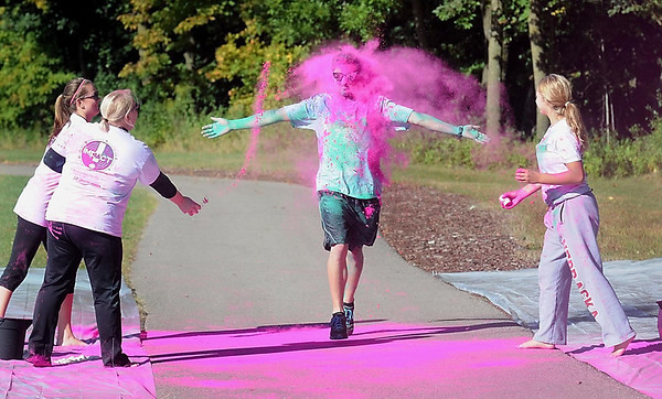 Pat Christman <br /> Volunteers, from left, Morgan Romery, Crystal Berg and Paige Welch throw pink powdered dye at a runner during the Color Rush 5k race Saturday at Minnesota State University.