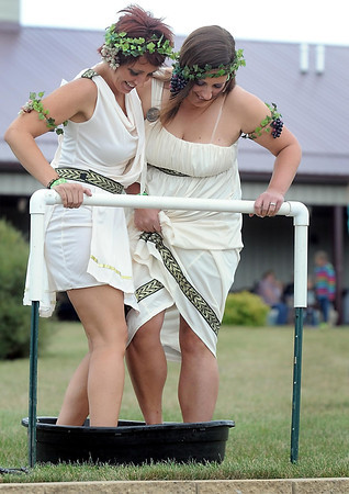 Pat Christman<br /> Brandi Rossow, left, and Michelle Beck dressed in Greek atire for their turn stomping grapes Saturday at Indian Island Winery.