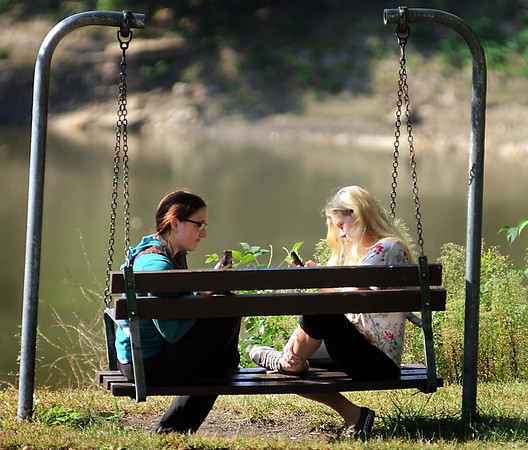John Cross<br /> It was not as it appeared as West High classmates and friends Ava Peterson (left) and Autumn Olson seem deep into texting while soaking up some Wednesday sunshine at Sibley Park. In fact, Olson was feigning texting while Peterson video taped another nearby classmate. It was all part of an experiment for their psychology class _ which is all to complicated to explain in a brief picture caption.
