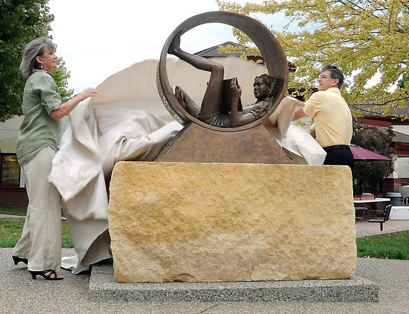 """Pat Christman <br /> Artist Karen Crain and North Mankato mayor Mark Dehen unveil Crain's sculpture """"Circle of Friends"""" in front of the North Mankato Taylor Library Thursday."""