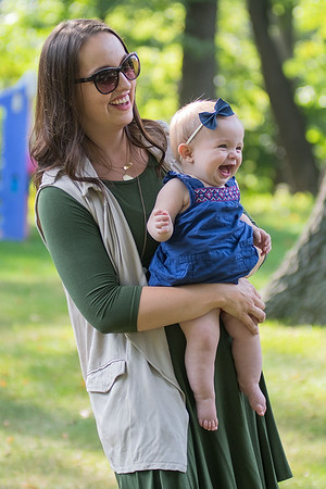 Jessica Blais holds her daughter Clara, 7 months, as Clara gets a kick out of watching her brother Noah and her father George play football in their backyard. Blais runs the Mankato Moms Blog, a parenting resource that launched on Aug. 16. Photo by Jackson Forderer