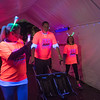 Participants in the Camp Sweet Life Glow in the Park 5K walk through a blacklight tent that made their shirts and other accessories turn neon colors. The even held in Sibley Park on Saturday benefits a summer camp for children with Type 1 diabetes. Photo by Jackson Forderer