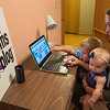 "Noah Blais, 5, points to a picture on the Mankato Moms Blog while his mother Jessica Blais holds Clara Blais, 7 months, at their home in Mankato. Blais runs the blog with contributions from 17 writers and said that the biggest thing she has learned is ""hearing from other moms that have different experiences than you have and being able to take away and apply that to your own motherhood journey."" Photo by Jackson Forderer"