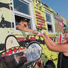Karen Toft (right) gets her food order from Nam Dao with the K-Town food truck in the Food Truck Hub next to the Hubbard Building along Riverfront Drive. K-Town serves up Korean fusion food to its customers. Photo by Jackson Forderer