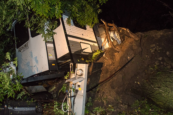 An uprooted tree pushed a camper onto its side at Kamp Dels in Waterville after a large storm blew through the area on Thursday evening. Photo by Jackson Forderer