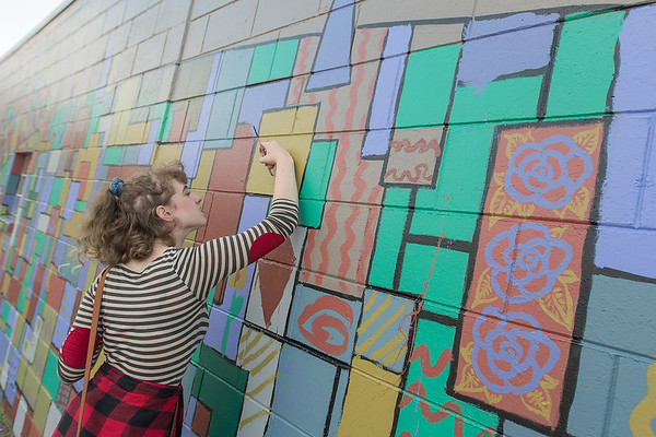 Taylor Weir paints on a section of a new mural being painted in Old Town as part of the Art Fair on Saturday. Weir's parents run the business Institute for Environment Assessment, on which the mural is being painted on along Riverfront Avenue. Photo by Jackson Forderer