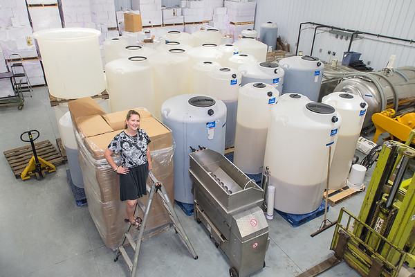 Angie Metzke, next to fermentation vats, is a wine maker at Indian Island Winery. The winery celebrated it's 9th annual Grape Stomp and Vendor Show, which marks the middle of their harvest. Photo by Jackson Forderer