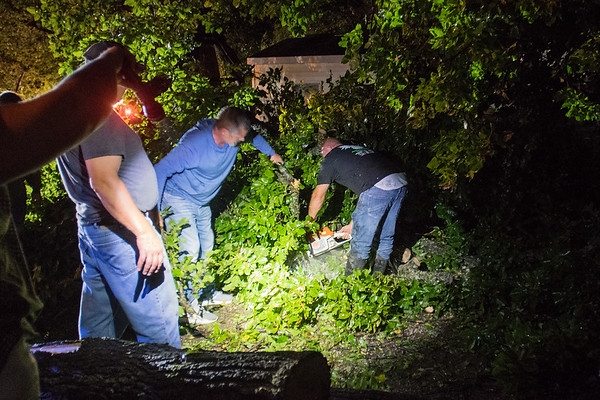 Brian Wencl (right) of Owatonna uses a chainsaw to cut through a tree that fell near a house at Kamp Dels in Waterville as the cleanup process began in the area on Thursday evening. Photo by Jackson Forderer