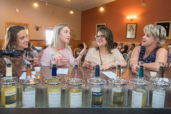 From left, Katie Williams, Jenna Boelter, Brenda Kremer and Julie Boelter talk while wine tasting at Indian Island Winery on Saturday. The winery held their 9th annual Grape Stomp and Vendor Show on Saturday. Photo by Jackson Forderer