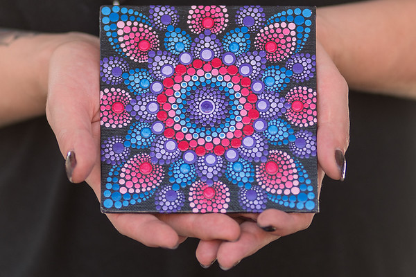 Heather FitzSimmons holds a mandala she painted that was for sale at the Old Town Art Fair on Saturday. FitzSimmons was one of many vendors selling their artwork and crafts. Photo by Jackson Forderer