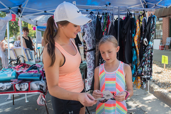 Nicole Nelson (left) and Romey Hinz, 8, look at earrings in a vendor's booth during the Old Town Art Fair held on Saturday. The fair included vendors, music, and a new mural being painted in Old Town. Photo by Jackson Forderer