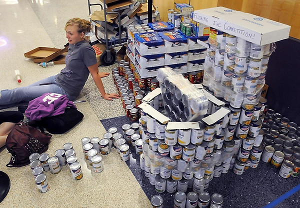 Jacky Brungardt sits near Sigma Sigma Sigma and Lambda Chi Alpha's sculpture of a toilet made from cans of donated food during a canned food sculpture contest Thursday at Minnesota State University. The contest was part of homecoming week activities.