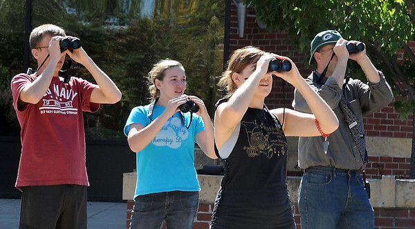 From left, students Daniel Halvorson, Alex Oldenburg and Becky Riediger and biology professor Chad Heins keep an eye on a broad-winged hawk over Bethany Lutheran College.