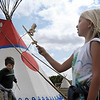 Loyola students Emily Hiniker and Joe Griffith try their hand at a traditional Dakota children's game during education day Friday at the 40th annual Mahkato Wacipi at Land of Memories Park.
