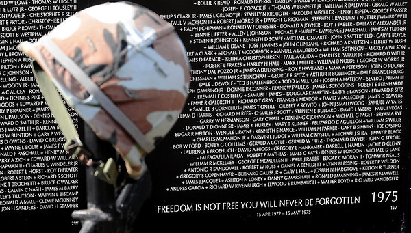 A helmet and rifle stand in front of a section of the traveling Vietnam veterans memorial wall at the Vietnam Veterans Memorial site in Mankato.