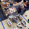 Lisa Miller puts the finishing touches on her team's canned food sculpture, a boot stomping on the Concordia-St. Paul bear mascot, Thursday.