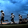 Pat Christman <br /> Members of the Mankato East football team run onto the field under cloudy skies before their game against crosstown rival Mankato West Friday at MSU's Blakeslee Stadium.