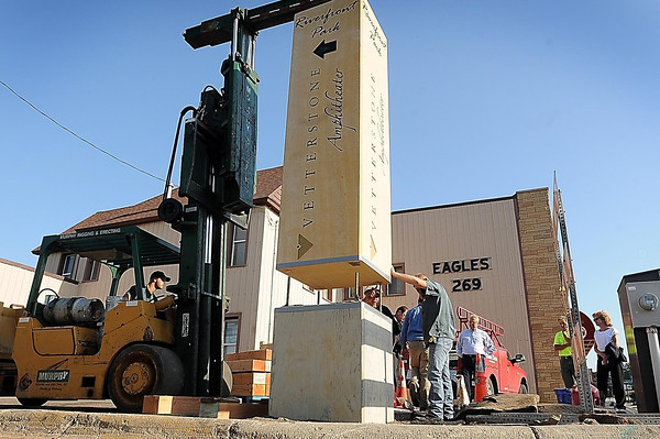 John Cross<br /> Workers guide a Kasota stone sign directing visitors to Riverfront Park into place at the corner of North River Front Drive and Rock Street on Thursday. The 16,000-pound sign was donated by Vetter Stone.